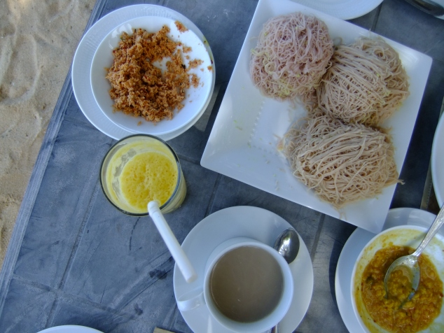 A typical Sri Lankan breakfast: hoppers (noodles), curry and coconut sambal