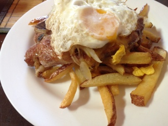 Pork chop, fried onions, fried egg, chips, Chile
