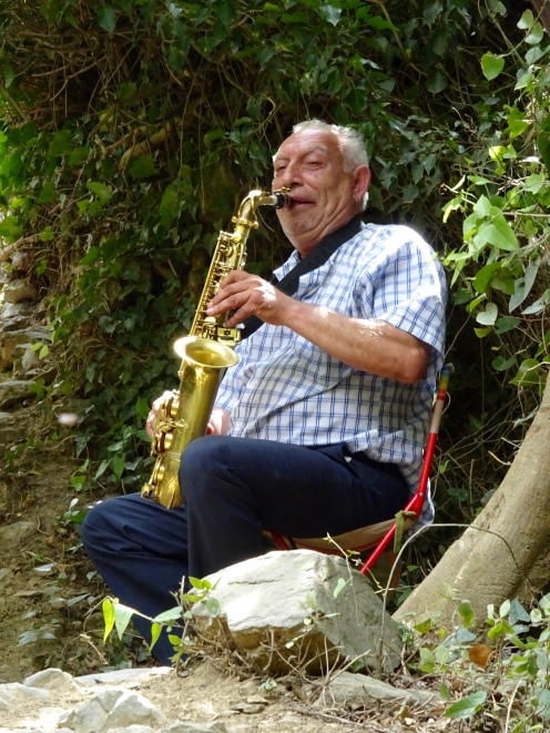 Man playing a sax on the path